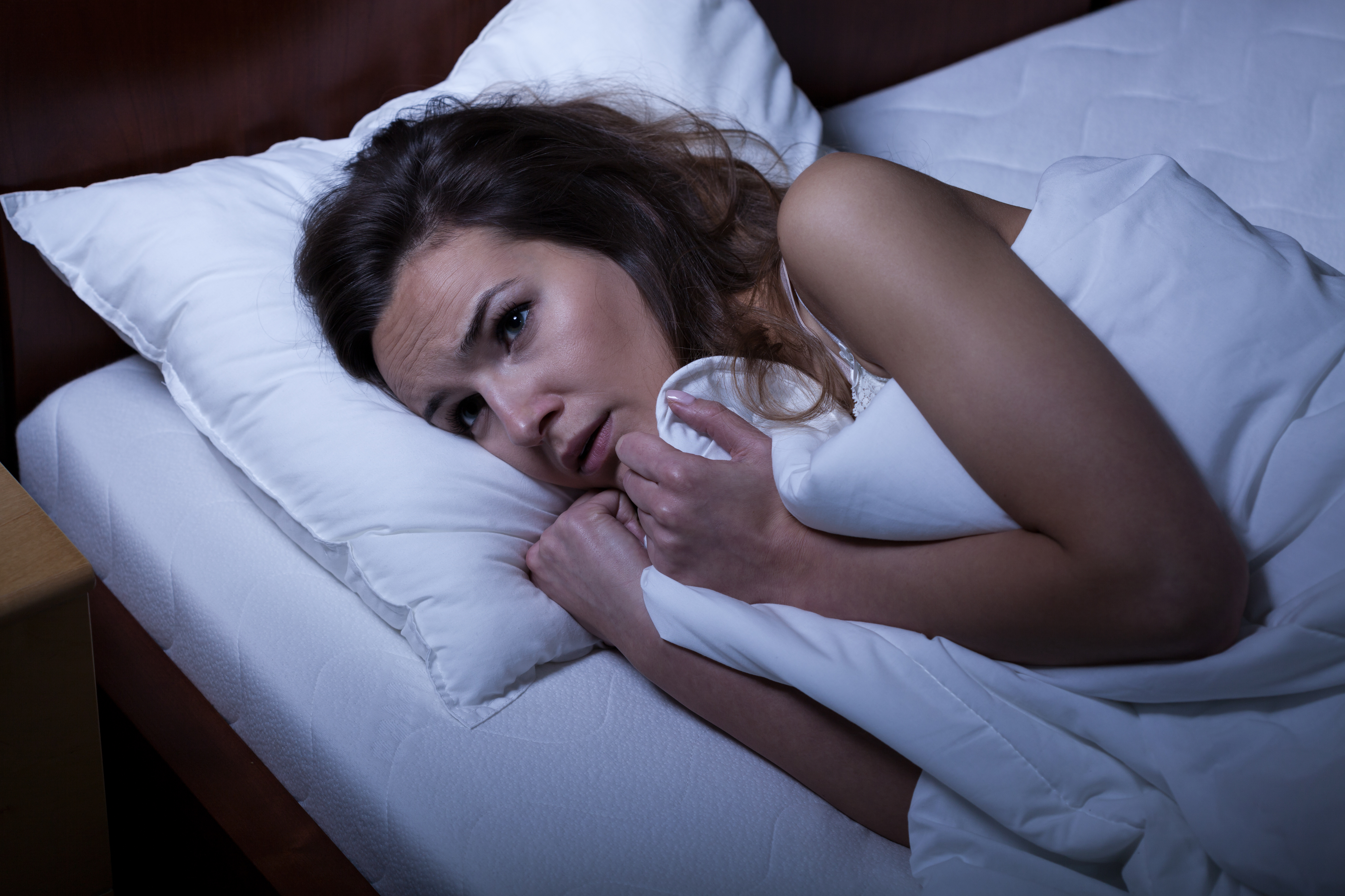 Image of scared woman trying to sleep