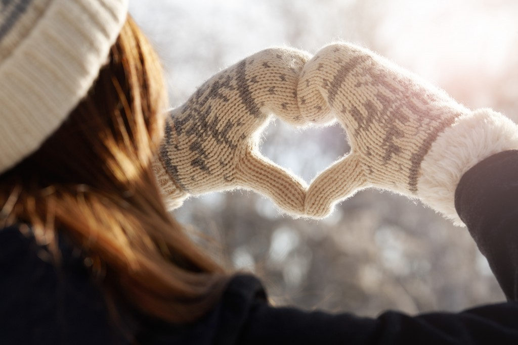 Young woman in winter mittens holding hands in a heart shape against the sunlight, feelings concept