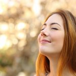 woman doing breath exercises with an autumn background